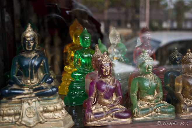 Coloured glass and stone Buddha images in a shop window, Luang Prabang