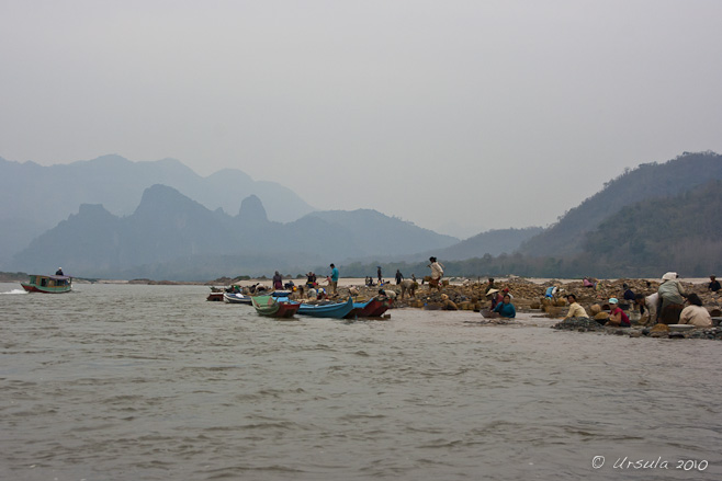 View of people and long wooden boats on sandbars on the river: ragged karst mountains in the background.
