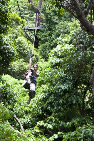 Laughing woman on a cable hipline over jungle