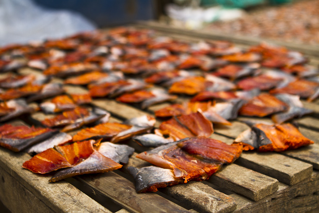 Chunks of red fish lying in the sunshine on wooden slats.