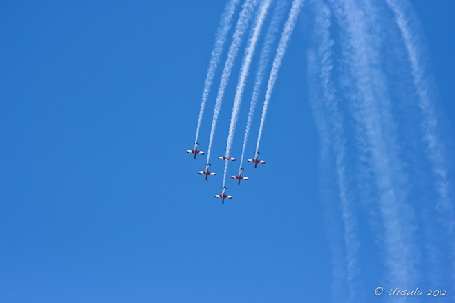 Six red and white PC-9/A ( two-seat single-engine turboprop aircraft) flying downward in triangle formation; vapour trails behind.