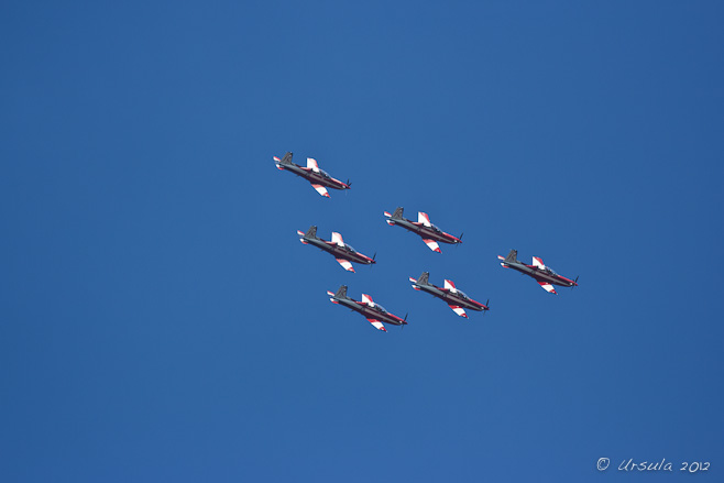 Six red and white PC-9/A ( two-seat single-engine turboprop aircraft) flying downward in triangle formation.
