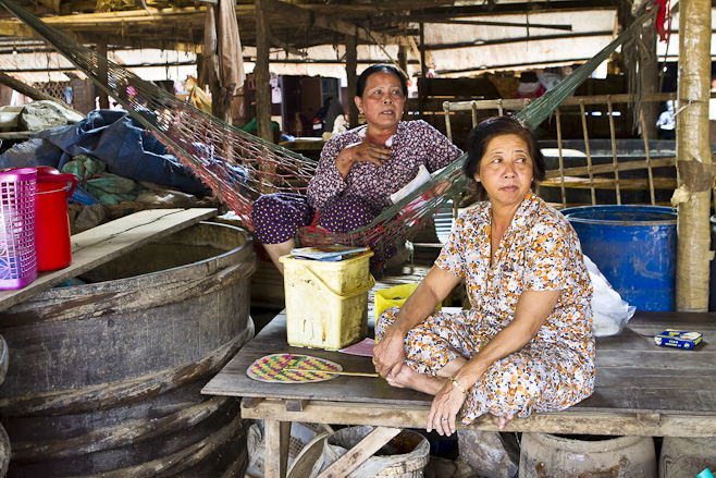Two khmer women in cotton dresses sitting in a large warehouse-like building.