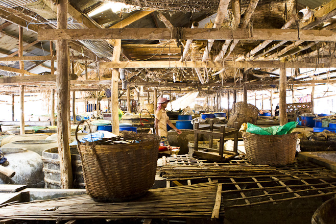Clay pots, wooden beams and wicker baskets in a khmer fish-paste factory.
