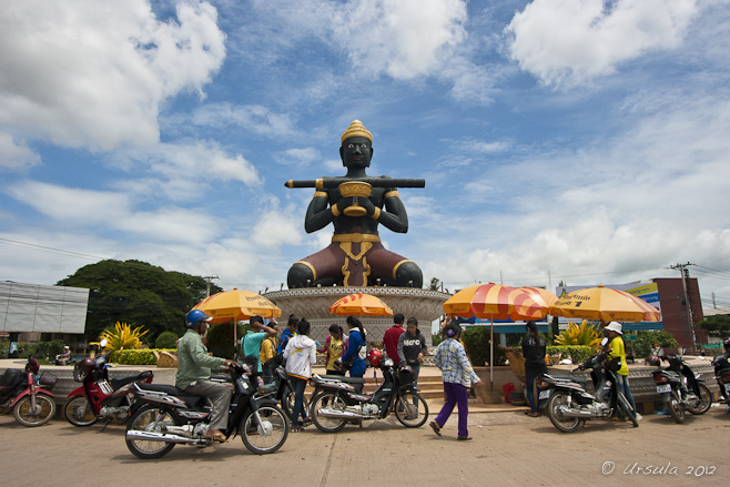 Large  statue of a Khmer King with a large stick sits in a central circus in Battambang.