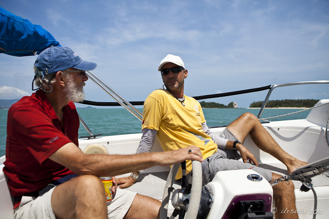Two men at the helm of a small sailboat.