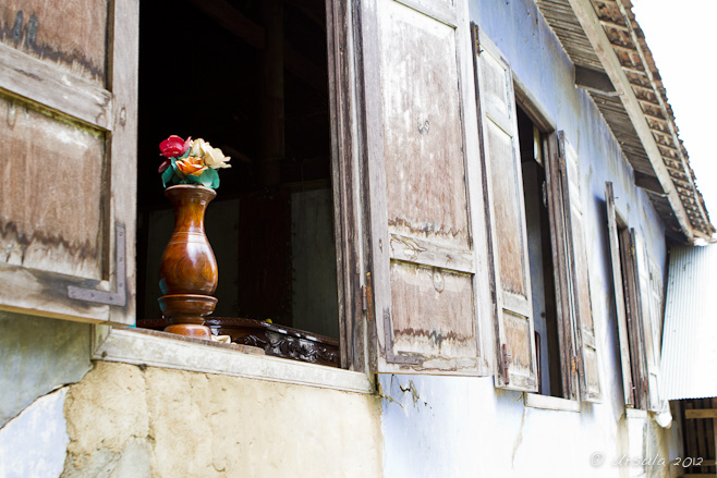 Artificial flowers in a wooden vase in and open window with wooden shutters.