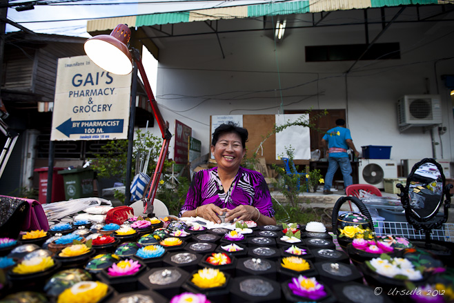 Smiling Thai woman sitting at a table of colourful carved soaps.