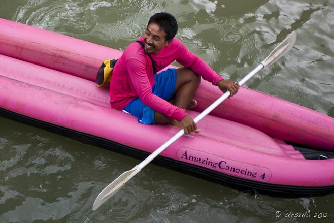 Thai man in hot pink shirt in a hot pink sea kayak.