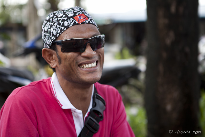 Portrait: Thai man in skull-and-crossbones headscarf and sunglasses.