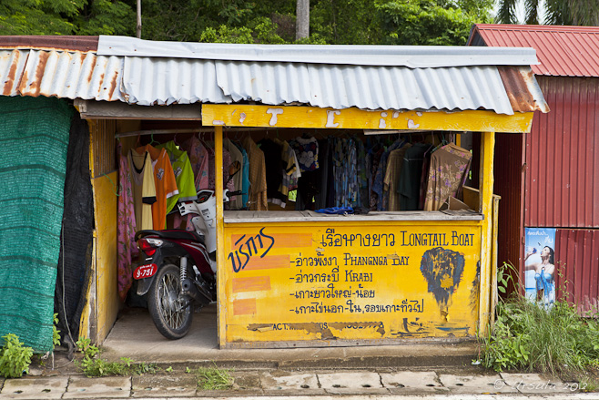 Yellow tour-shop hut front: motorcycle parked in the doorway.