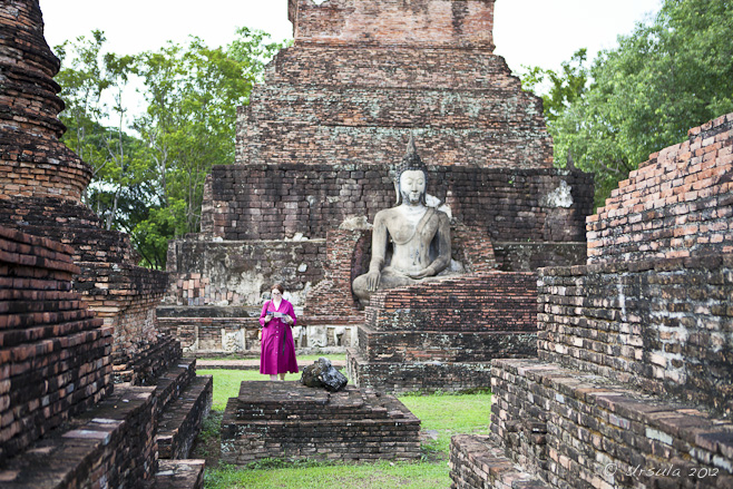 A woman in a hot pink dress among the red-laterite ruins of Sukhothai.