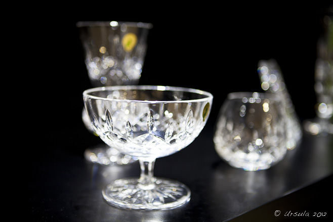 Crystal sweet bowl and wine glass against a black background.