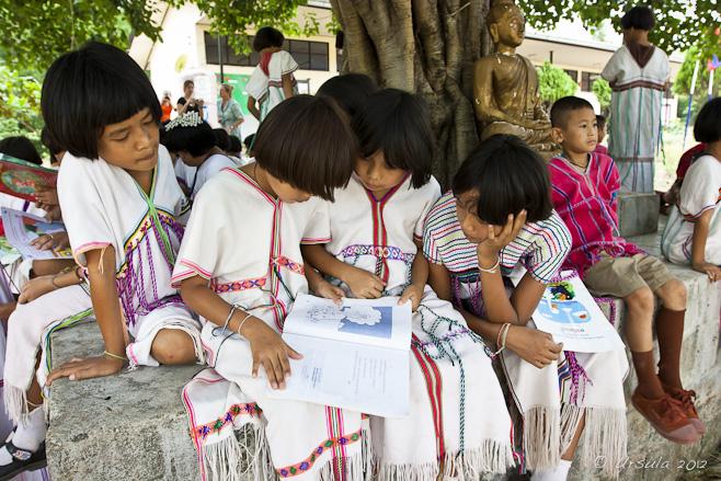 Karen Thai students grouped around a book.