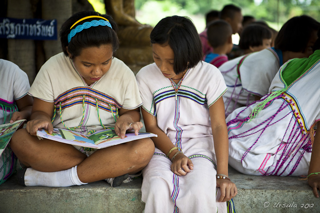 Young Karen girls in traditional dress reading under a tree.