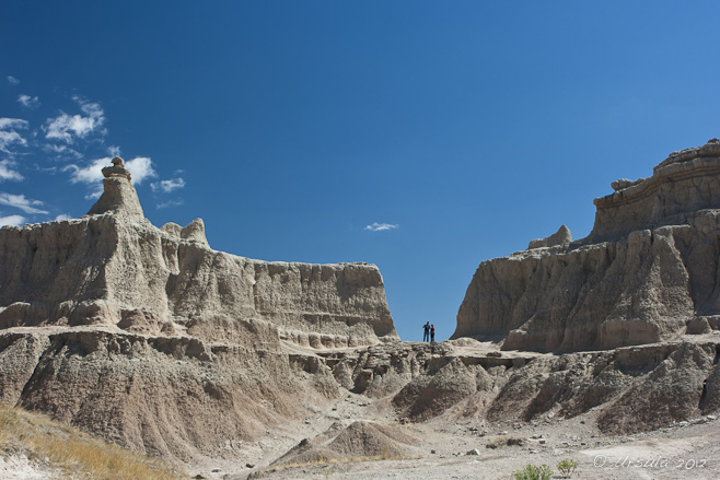 Two people are dwarfed by the rock formations of the SD badlands.