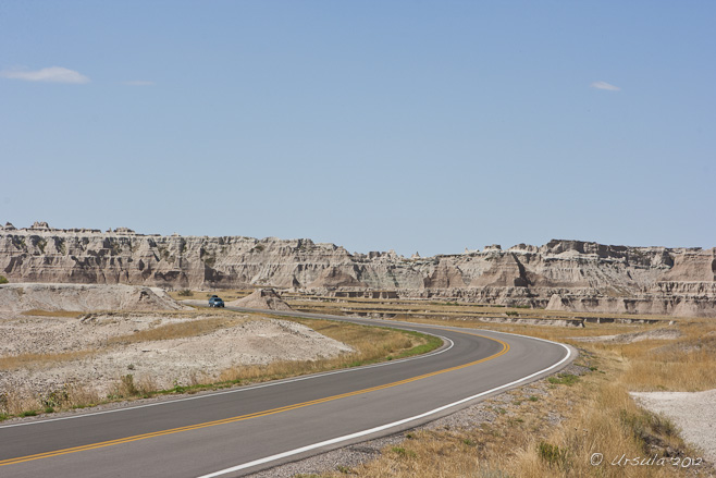 Curving road into dry badland mountains.