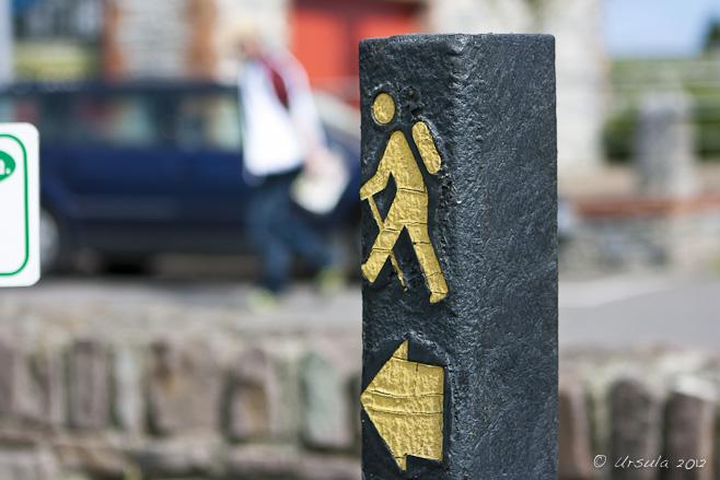 Yellow walking man on a black signpost.