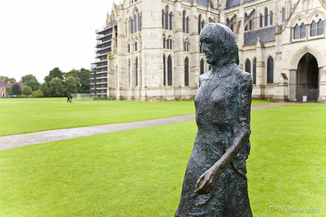 Sculpture of a woman walking on the green grass in front of Salisbury Cathedral.