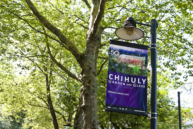 Purple poster for the Chihuly Garden and Glass Exhibition against trees.