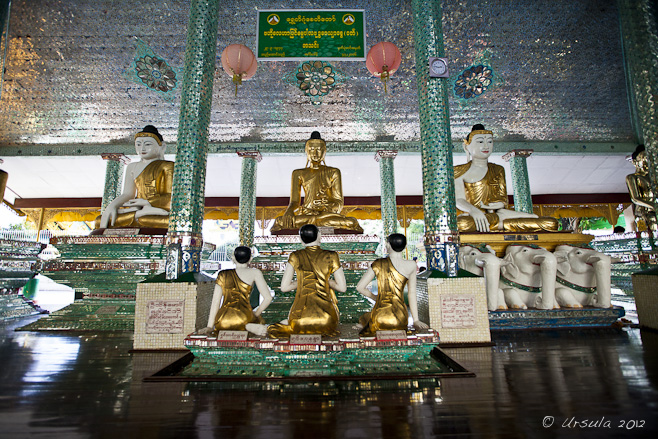 Large and small seated Burmese Buddhas in a lavishly tiled hall, Shwedagon.