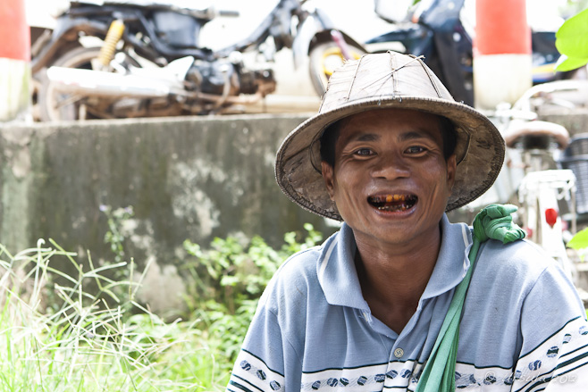 Portrait: Burmese man with beetle-juice teeth in woven bamboo hat