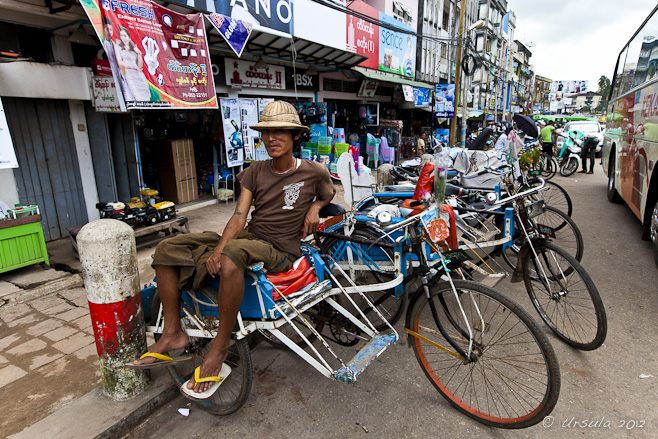 A burmese bicycle rickshaw driver sits on his vehicle in a busy market street. Bago, Myanmar