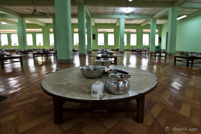 Low round table with tin tea pot and food bowls, Kyahkatwine Monastery, Bago, Myanmar