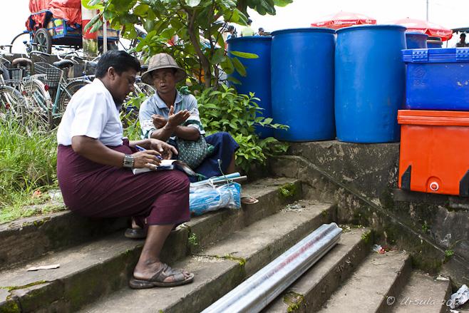 Two Burmese men sitting on cement steps; one telling a story, the other writing.