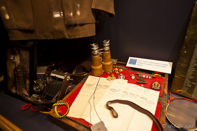 Museum display: papers, binoculars camera and clothing and medals from early 1900