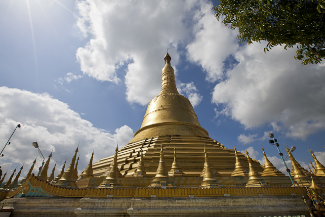 The golden Shwemawdaw Temple in afternoon light against fluffy white clouds. Bago (Pegu), Myanmar