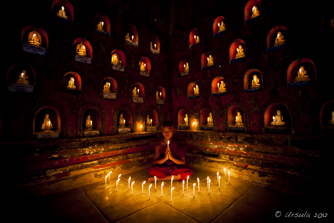 Young burmese monk surrounded by candle-lit alcoves with Buddhas in them, Shweyanpyay Monastery, Naung Shwae, Myanmar