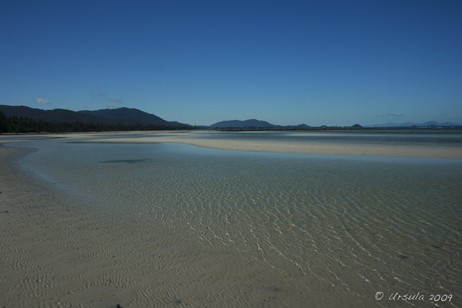Expanse of rippled sandy beach with a thin layer of water across it.