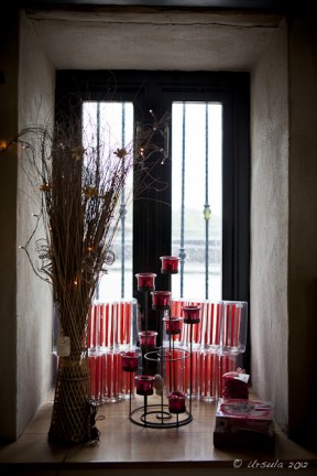 Red candle holders  and a vase of black reeds inside a black-framed window.