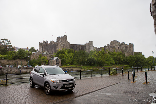 Pembroke Castle against a rainy sky; a parked car and the River Cleddau.