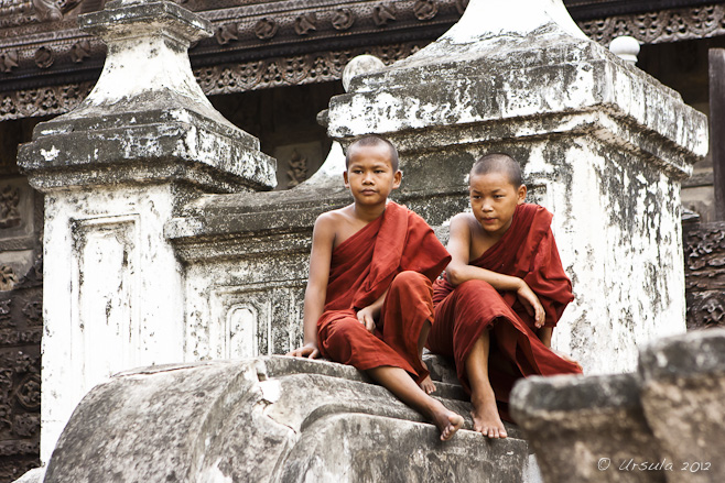 two young novice monks in maroon robes sitting on the stairs of Shwenandaw Monastery, Mandalay.