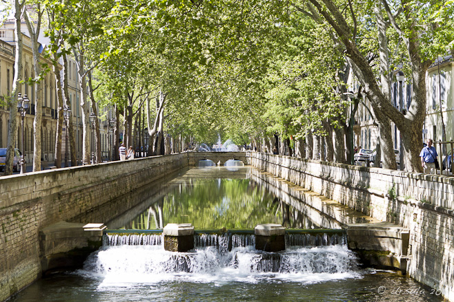 A canal with water wheels under an avenue of trees, Nîmes, France.