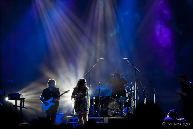 Dark blue stage with singer and band backlit by white light.