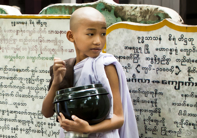 Young novice nun in White, clutching her alms bowl, looking over her shoulder. Mahagandayon Monastery, Mandalay