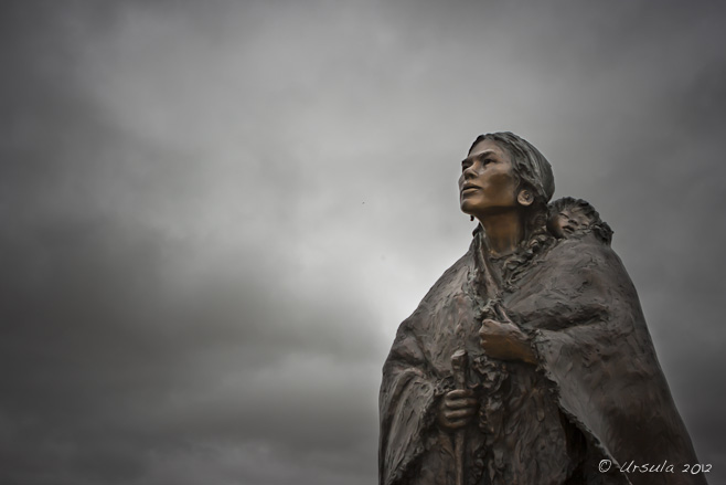 Sculpture of Sacagawea and baby Jean Baptist by Glenna Goodacre, against a gloomy grey sky; Buffalo Bill Historical Center, Cody, WY