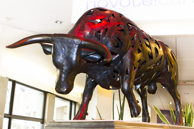 Modernistic sculpture of a bull under red and yellow light ~ Lucien Blanc