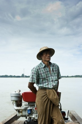 Burmese male in a pith hat and check shirt steering a motorboat Irrawaddy River
