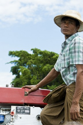 Burmese male in a pith hat and check shirt steering a motorboat Irrawaddy River.