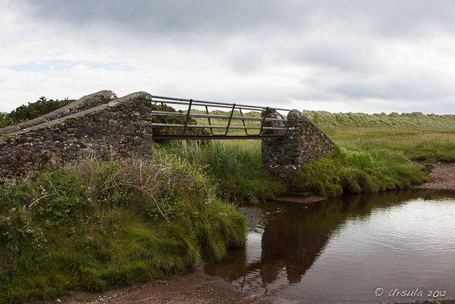 Small stone and metal bridge over a small, quiet creek; Castlegregory, Dingle Peninsula, Ireland