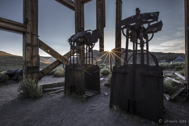 Sun rays through the wooden head frame and rusty man lifts, Bodie SHP, California, USA