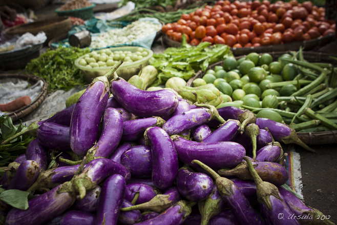 Purple eggplant, green limes, red tomatoes and other vegetables in baskets on the ground in an outdoor Mandalay street market.