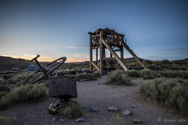 Rusty bits of machinery and an old wooden head-frame in dawn light, Bodie SP, CA, USA