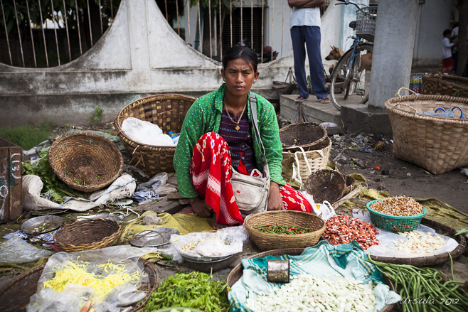 A Burmese woman sits on the ground in a street market, surrounded by her beans.