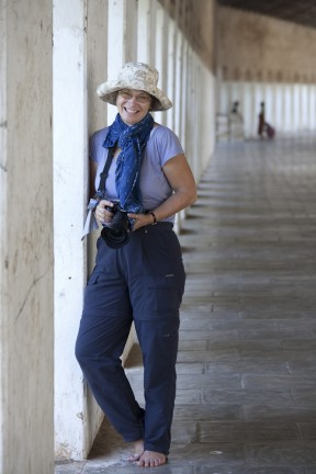 Woman, dressed in blue walk pants and scarf with a camera, in the corridor of a Bagan temple.