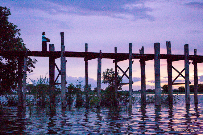 Evening scene on U-Bein Bridge: a woman with a basket stands on the wooden bridge, silhouetted against a purple sky, Amarapura, Myanmar